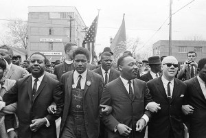 Dr. Martin Luther King, Jr. locks arms with his aides as he leads a march of several thousands to the court house in Montgomery, Ala., March 17, 1965. From left: Rev. Ralph Abernathy, James Foreman, King, Jesse Douglas, Sr., and John Lewis (partially out of frame). (AP Photo)